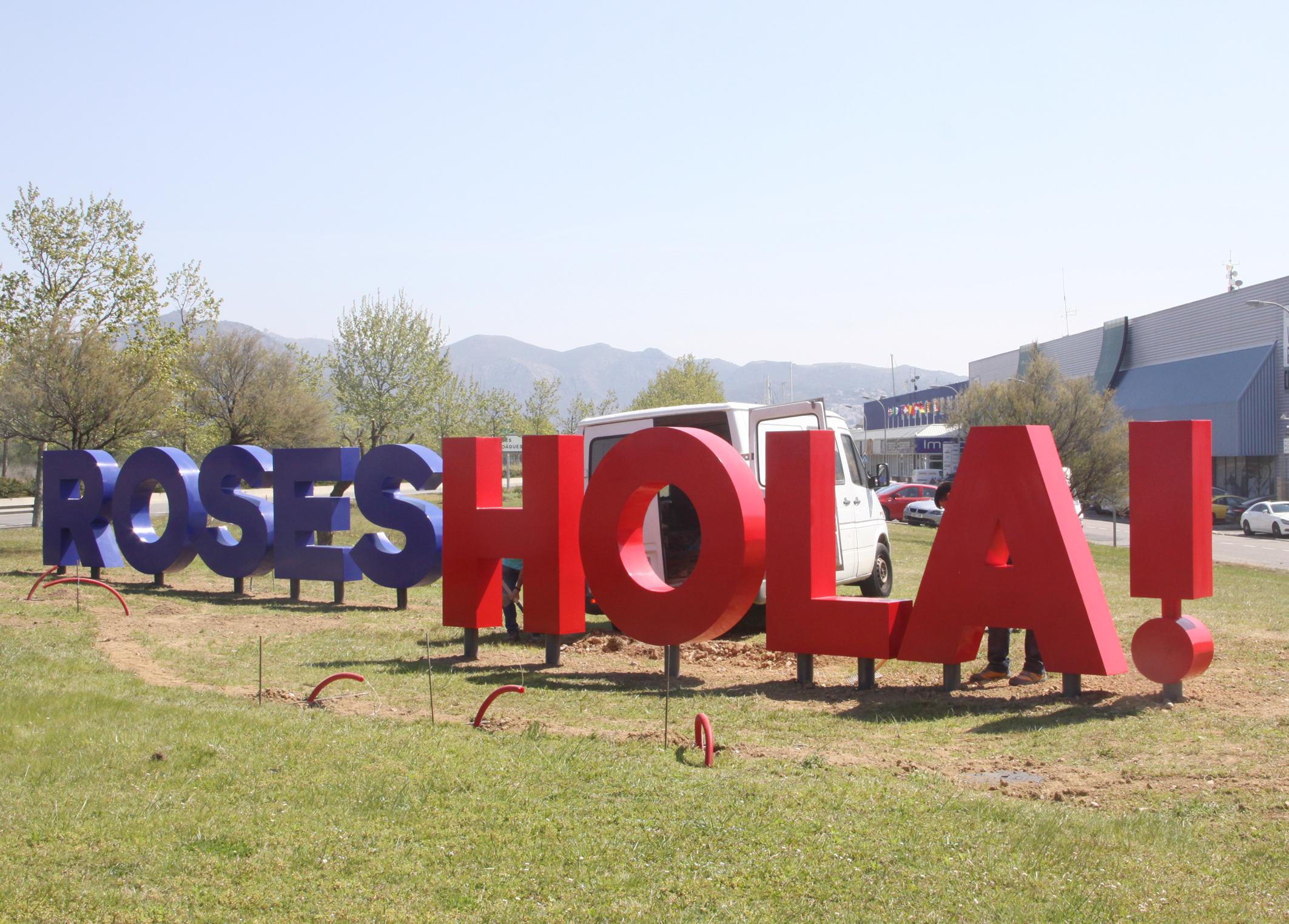 Un rètol de grans dimensions amb les paraules Hola! Roses dóna la benvinguda a la població