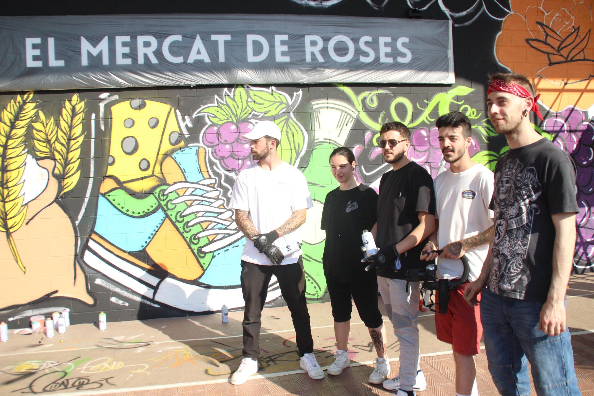 Set joves dibuixen un graffiti al Mercat Municipal de Roses per a commemorar el seu 35è aniversari